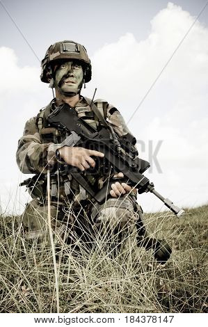 Normandy France- August 4 2011. Legionnaire in camouflage uniform with a rifle in the open area during tactical exercises.