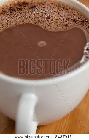 Close-up of white coffee cup with froth on wooden background