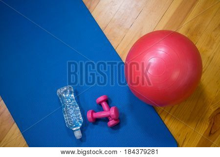 Fitness ball, water bottle, dumbbell and exercise mat on wooden floor in fitness studio