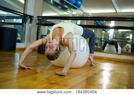 Fit woman exercising on fitness ball in fitness studio
