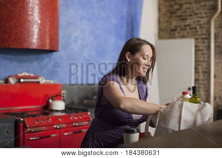 Pregnant Caucasian woman unpacking groceries in kitchen