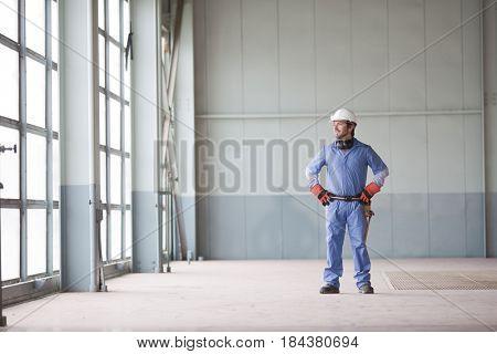Hispanic worker in hard-hat standing indoors