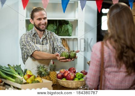 Smiling vendor offering custard apples to the woman in at the counter in grocery store