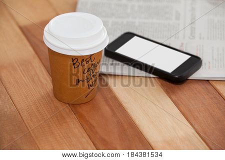 Close-up of disposable coffee cup, mobile phone and newspaper on wooden background