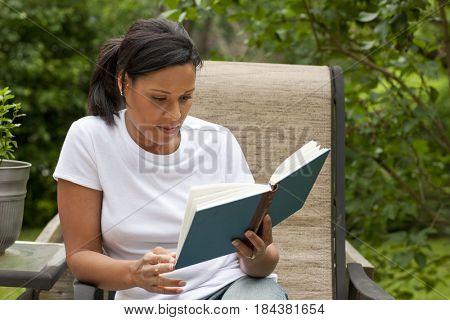 African American woman reading book in back yard