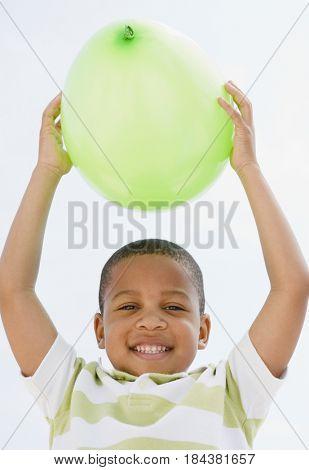 African American boy holding balloon above head