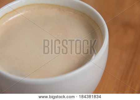 Close-up of white coffee cup with creamy froth on wooden background