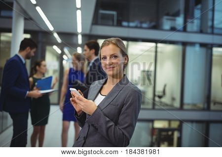 Businesswoman using digital tablet in the passageway at office