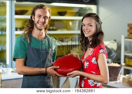 Portrait of salesman and costumer holding gouda cheese at counter in grocery shop