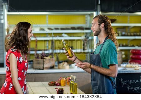 Shop assistant offering olive oil bottle to the customer at grocery shop