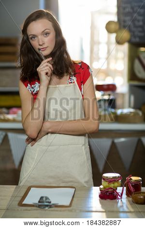 Thoughtful female shop assistant standing at the counter in grocery shop