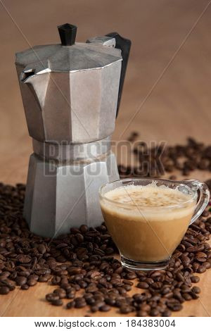 Coffee beans with metallic coffee maker and coffee cup on wooden background