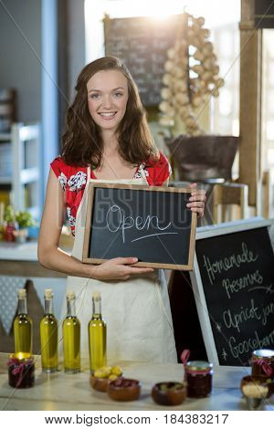 Female shop assistant holding open sign board at grocery shop