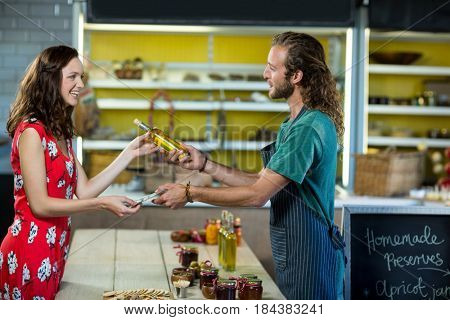 Shop assistant receiving payment from the customer at grocery shop