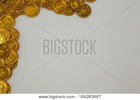 St Patricks Day gold chocolate coins forming corner frame on white background