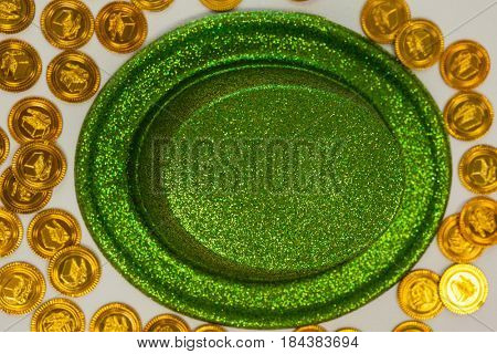 St Patricks Day leprechaun hat surround with gold chocolate coins on white background