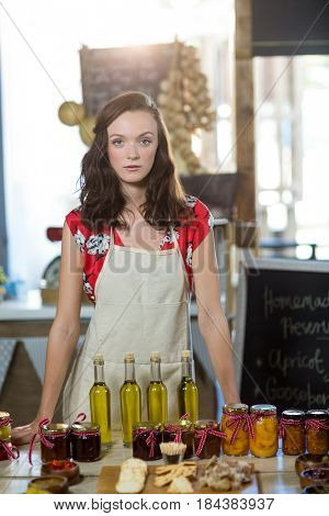 Portrait of a female shop assistant standing at the counter with pickle, olive oil and jam bottles at grocery shop