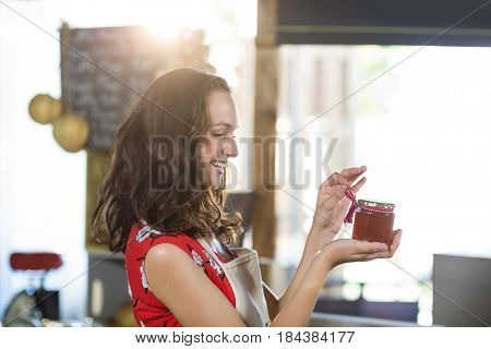 Female shop assistant looking a jar of jam at grocery shop