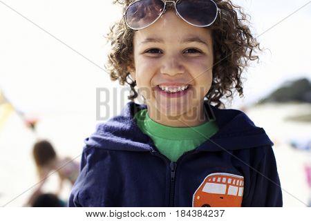Grinning mixed race boy on beach