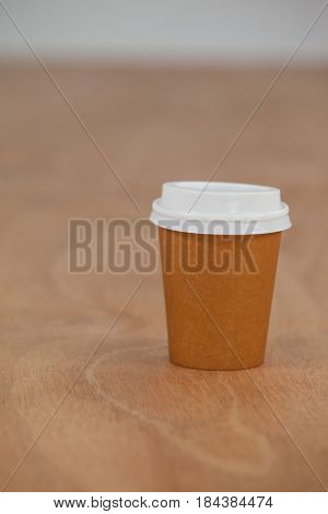 Take away disposable coffee cup on wooden background