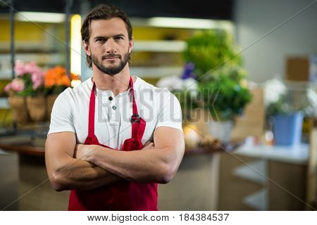 Portrait of a florist standing in florist shop with arms crossed