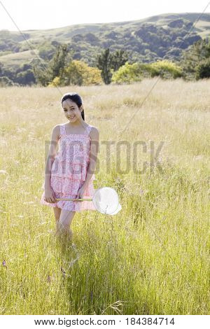 Hispanic girl in field holding net