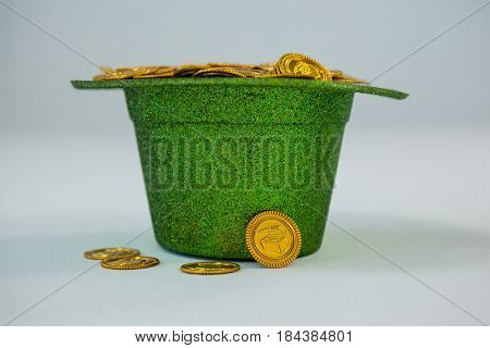 St. Patricks Day leprechaun hat filled with chocolate gold coins on white background