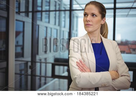 Thoughtful businesswoman standing with arms crossed in corridor in corridor