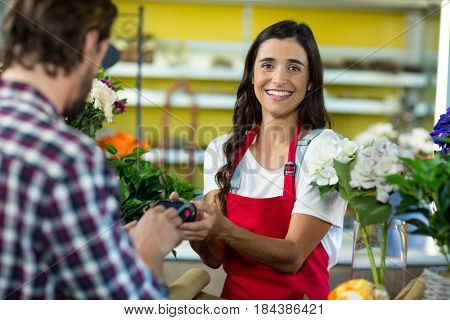 Portrait of a florist receiving a payment by credit card from the customer in the florist shop