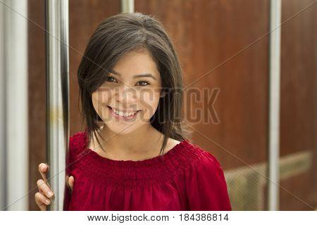 Smiling Hispanic woman standing near metal pole