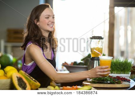 Smiling shop assistant offering the juice at the counter in health grocery shop
