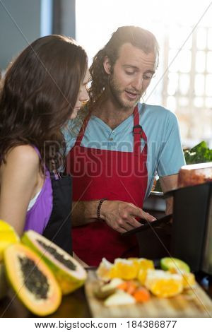 Two shop assistants discussing with digital tablet at health grocery shop