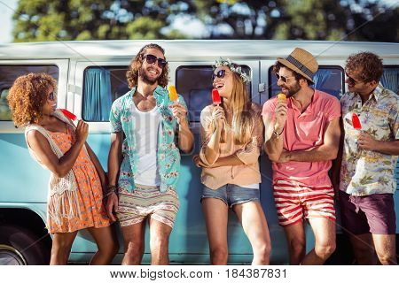 Group of happy friends standing with ice lolly in front of camper van in park