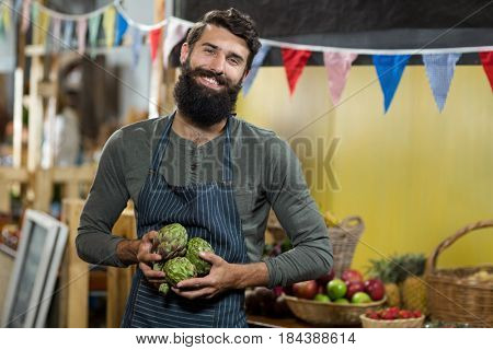 Portrait of a vendor holding custard apples at the grocery store