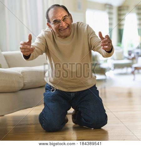 Smiling senior man kneeling with arms outstretched