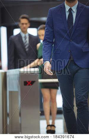 Mid-section of businessman passing through turnstile gate at office