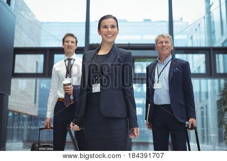 Business executives with trolley bag standing in the office