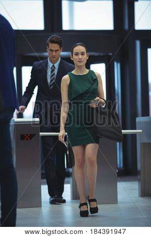Businesswoman passing through turnstile gate at office
