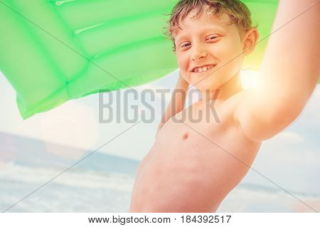 Smiling boy sea portrait with green air swiming mattress