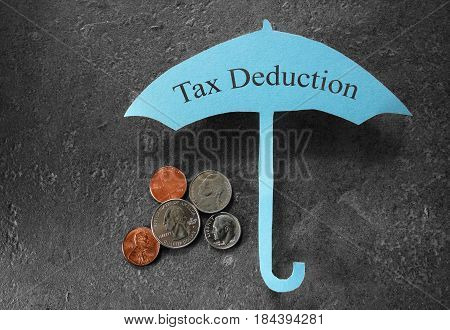 Coins under a paper Tax Deduction umbrella