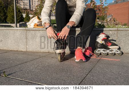 Girl puts on roller skates before skating in the park on a sunny morning. Female hands close-up.