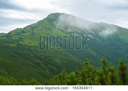 Magic mountain landscape. Ridge covered by a coniferous forest with mountain observatory on top misty morning.