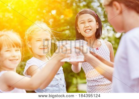 Group of girls drinking water in summer as friends at childrens birthday party