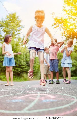 Girl jumps during hopscotch game with group of friends