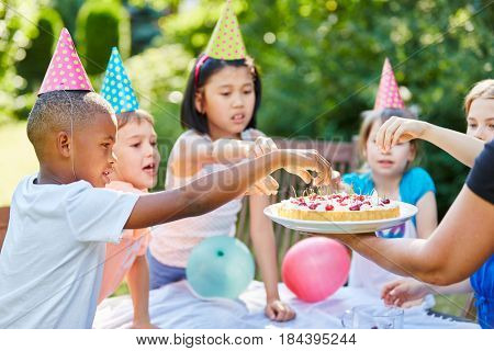 Interracial children children with cake at birthday party