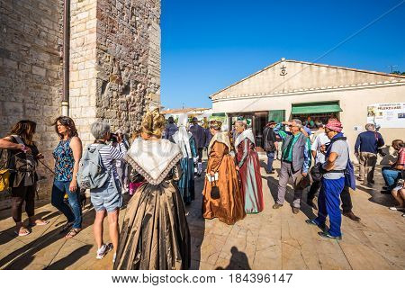Saint-Marie-de-la-Mer, Provence, France - May 25, 2015. World Festival of Gypsies. Participants of a carnival in medieval suits and city visitors. Medieval cathedral Notre Dame.