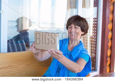 Smiling Woman Is Sitting On The Veranda Using Tablet