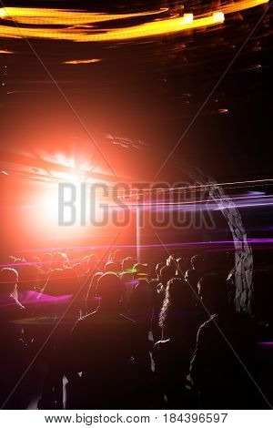 Young people with energy at party with abstract background of motion lights music party celebration in night or disco club. Nightlife and entertainment