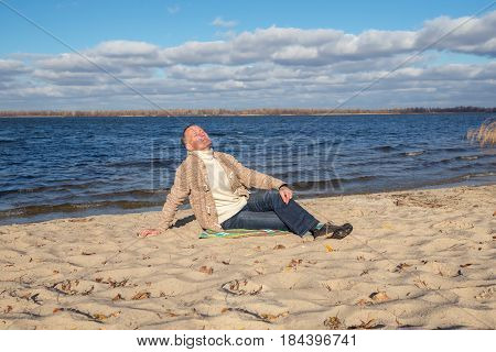Man Is Sitting On The River Bank And Enjoying Life
