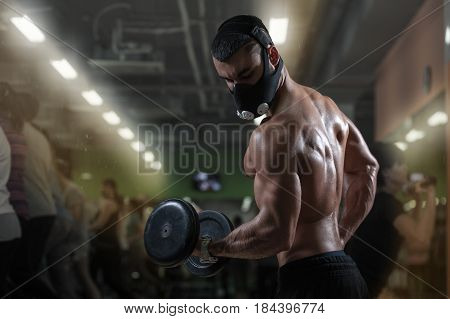 Muscular bodybuilder wearing training mask working out in gym doing exercises with dumbbells at biceps. Strong man with perfect body. Bodybuilding and fitness concept.
